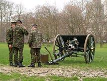 Soldados por un arma viejo de la guerra Fotografía de archivo