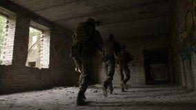 Soldados que asaltan el edificio capturado por el enemigo almacen de video