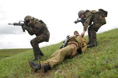 Soldados que conservam seu sócio ferido Imagem de Stock