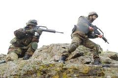Soldados que mueven encendido la montaña con los armas Fotos de archivo libres de regalías