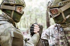 Soldados que sacuden las manos en bosque Fotografía de archivo
