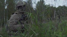 Soldados que se sientan en espera en la hierba Militares en armas sobre la colina almacen de metraje de vídeo