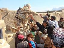 Soldados que trazem a ajuda em Afeganistão Imagem de Stock Royalty Free