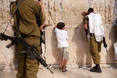 Soldados y niño israelíes en la pared occidental de Jerusalén Foto de archivo libre de regalías