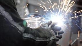 Soldadura de las estructuras del metal en la empresa industrial El soldador produce las estructuras de soldadura almacen de metraje de vídeo