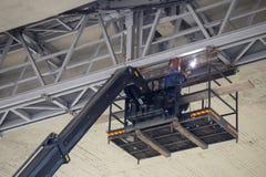 Soldadura de un marco metálico debajo del puente foto de archivo