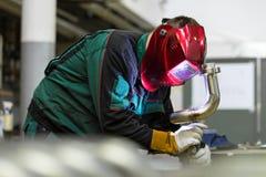 Soldadura do trabalhador industrial na fábrica do metal foto de stock