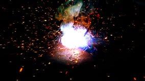 A soldadura elétrica industrial pisca close-up em um fundo preto filme