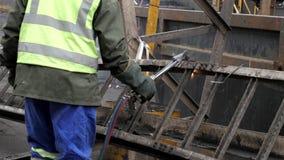 Soldadura industrial del trabajador del metal que corta un pedazo del metal grande 4k metrajes