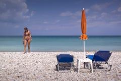 Soldagdrivare och paraply på den tomma sandiga stranden Royaltyfri Bild
