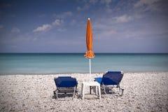 Soldagdrivare och paraply på den tomma stranden Royaltyfri Fotografi