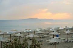 Soldagdrivare och paraply på en sandig strand Arkivbilder