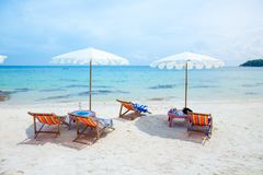 Soldagdrivare och strandparaplyer på stranden Royaltyfri Fotografi
