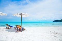 Soldagdrivare och strandparaplyer på stranden Arkivfoton