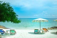 Soldagdrivare och strandparaplyer på stranden Arkivbilder
