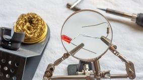 Soldando um resistor e um diodo emissor de luz com uma lupa, com os agrafos que guardam os componentes fotografia de stock