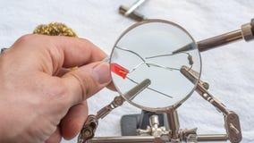 Soldando un resistor y un LED con una lupa, con los clips de cocodrilo llevando a cabo los componentes imagen de archivo libre de regalías