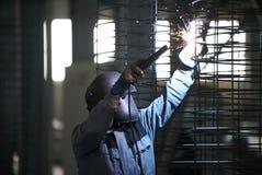 Soldas do homem do soldador na fábrica imagem de stock royalty free