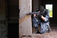 Soldat armé dans le masque noir visant avec un canon photos libres de droits