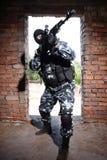 Soldat armé dans le masque noir visant avec un canon photos stock