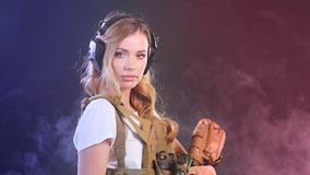 Soldat armé de femme dans l'uniforme militaire de camouflage protégé avec des écouteurs clips vidéos