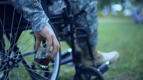 Soldat blessé dans le fauteuil roulant tenant le désordre d'effort posttraumatic en verre de whiskey banque de vidéos