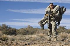 Soldat Carrying Wounded Friend för USA-armé Arkivbilder