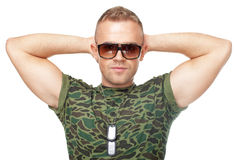 Soldat d'armée dans des lunettes de soleil avec des mains derrière sa tête Photos libres de droits
