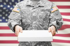 Soldat d'armée des Etats-Unis tenant le boîtier blanc avec deux mains Image stock