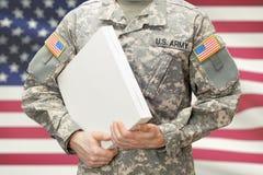 Soldat d'armée des Etats-Unis tenant le grand boîtier blanc avec deux mains images libres de droits