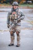 Soldat dans la vitesse protectrice avec un fusil dans des ses mains image stock