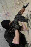 Soldat dans le masque noir déménageant en haut avec le fusil images stock