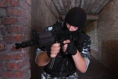 Soldat dans le masque noir visant avec un canon photographie stock libre de droits