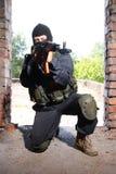 Soldat dans le masque noir visant avec un canon image stock