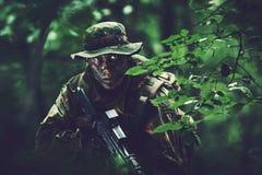 Soldat dans le secteur de forêt au crépuscule image stock
