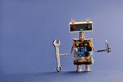 Soldat de robot avec la clé et le tournevis de main sur le fond bleu Travailleur mécanique abstrait de jouet fait en électronique Images libres de droits