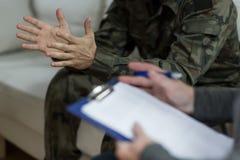 Soldat, der auf dem Sofa sitzt Stockbild