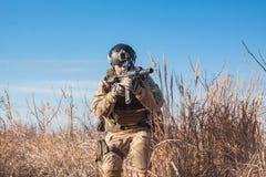 Soldat, der in Büsche mit Gewehr läuft Lizenzfreie Stockbilder