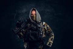 Soldat der besonderen Kräfte in tragender Maske der Militäruniform und Haube, die mit einem Sturmgewehr aufwirft stockfoto