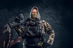 Soldat der besonderen Kräfte in tragender Maske der Militäruniform und Haube, die mit einem Sturmgewehr aufwirft stockfotografie