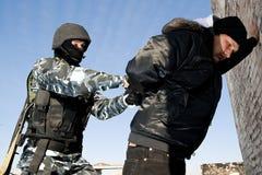 Soldat, der einen Verbrecher unter Anhalten nimmt Lizenzfreies Stockfoto