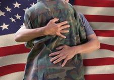 Soldat, der Familie vor USA-Flagge umarmt Stockfotos