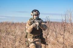 Soldat, der mit Gewehr auf dem Gebiet geht Lizenzfreies Stockbild