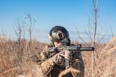 Soldat, der mit Gewehr sitzt Lizenzfreie Stockbilder