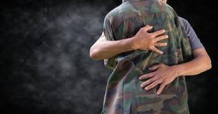 Soldat, der mittleren Abschnitt gegen schwarzen Schmutzhintergrund umarmt stockfotos