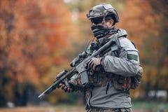 Soldat in der Schutzkleidung und Sturzhelm, der ein Gewehr hält lizenzfreies stockfoto