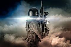 Soldat in der Uniform mit Gewehr, Angriffsscharfschütze auf apokalyptischen Clo stockfotografie