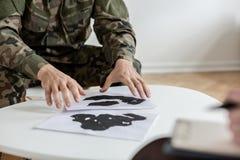 Soldat i den gröna moro likformign som väljer bilder under terapi med psykiatern royaltyfri bild