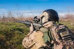 Soldat im Hinterhalt, der mit Gewehr zielt Lizenzfreie Stockfotos
