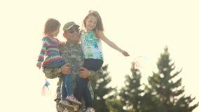 Soldat marchant tenant deux petites filles adorables en parc banque de vidéos